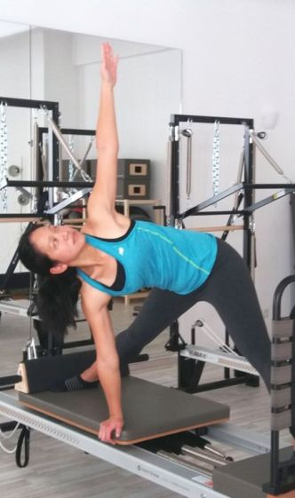 a woman performing a yoga pose on Pilates Reformer