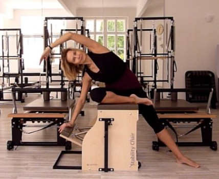 a woman performing mermaid exercise-on-Pilates chair