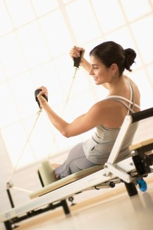 a woman performing Pilates exercise on Reformer